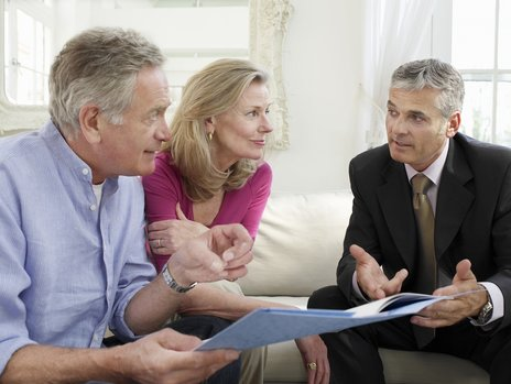 A senior citizen couple having a consultation with an male agent wearing a suit